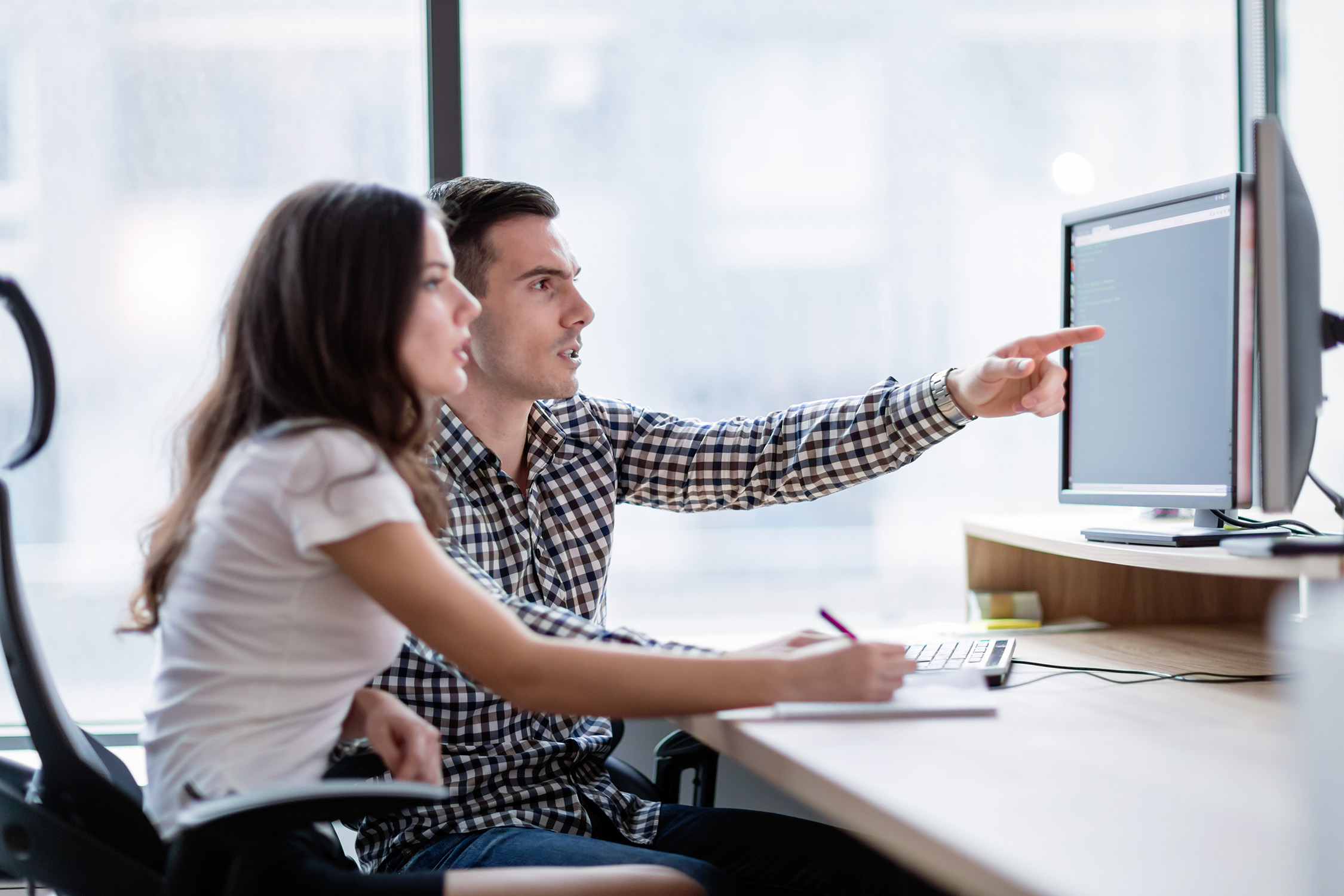Two young business colleagues working on computer together